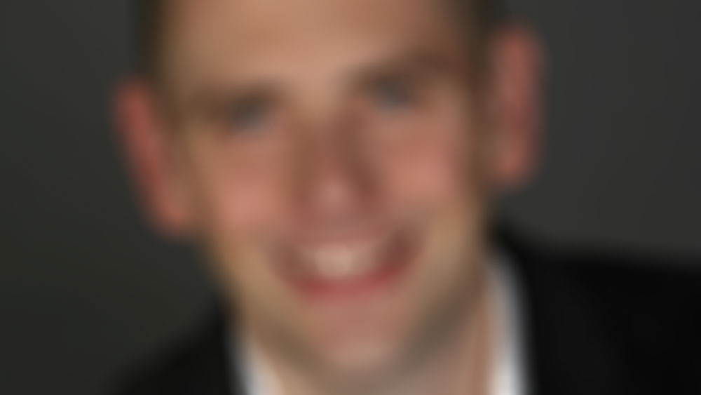 Blurry picture of Skepticon 8 speaker Bo Bennett's headshot that is used as a background photo on the website because we're fancy like that.