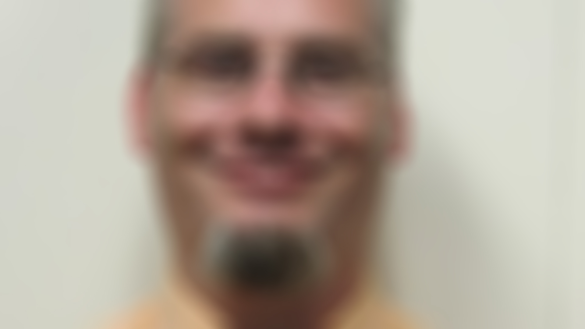 Blurry picture of Skepticon 8 speaker Justin Vollmar's headshot that is used as a background photo on the website.